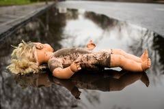 Encontro plástico da boneca de face para cima em uma poça rasa pela borda da estrada fotos de stock royalty free