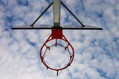 Encosto de basquetebol velho da negligência com a aro oxidada acima da corte da rua Céu nebuloso azul no bckground filtro retro Fotos de Stock