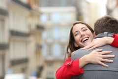 Encounter of a happy couple in the street in winter stock photos