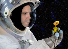 Encounters with extraterrestrial civilizations. Astronaut holding in glove alien on background of stars stock photo