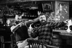 Encourage le concept Alcool potable d'homme barbu brutal de hippie avec l'ami au compteur de barre D?tente bue par hommes au bar  images libres de droits