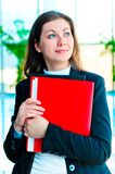 Encouraged by a businesswoman holding a red folder with documents Royalty Free Stock Images