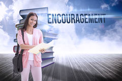 Encouragement against stack of books against sky. The word encouragement and pretty student smiling at camera against stack of books against sky royalty free stock photo