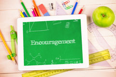 Encouragement against students desk with tablet pc. The word encouragement and math and science doodles against students desk with tablet pc Royalty Free Stock Images