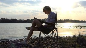 Young Man Sits on a Chair And Writes His Masterpiece on a Riverbank stock footage