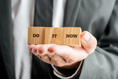 Encouraging message Do it now. Closeup of personal motivator holding three wooden cubes aligned on the palm of his hand saying Do it now encouraging you to take Stock Photo