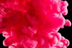 Encre dans l'eau Encre tourbillonnant dans l'eau Encre dans l'eau d'isolement Encre rose dans l'eau sur un fond noir Image libre de droits