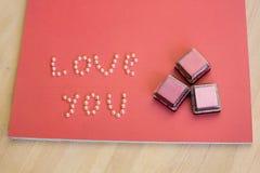 Encres colorées de colorant pour les perles scrapbooking et une inscription je t'aime sur une table en bois Images libres de droits