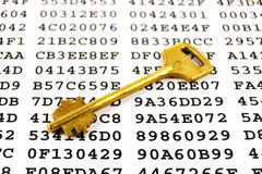 Encryption key. Golden key on a sheet with encrypted data Stock Photo