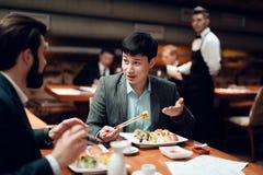 Encuentro con de hombres de negocios chinos en restaurante Dos hombres están comiendo el sushi Fotografía de archivo