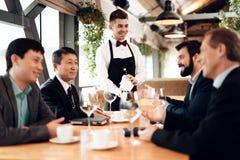 Encuentro con de hombres de negocios chinos en restaurante El camarero trae el vino imágenes de archivo libres de regalías