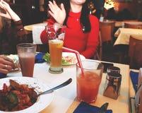 Encuentro de amigos de mujeres en el restaurante para la cena Las muchachas relajan y beben los cócteles fotos de archivo libres de regalías