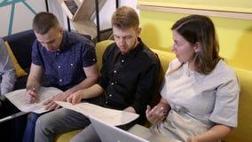 Encuentro de los oficinistas Los colegas discuten el plan que se sienta en el sof? por la tabla almacen de metraje de vídeo