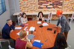 Encuentro en la oficina En la mesa redonda el equipo se sienta, y al lado de él hay un jefe en un casco imagen de archivo libre de regalías