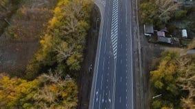 Encuesta aérea vuelo a lo largo de la última carretera del otoño marcas de camino brillantes metrajes