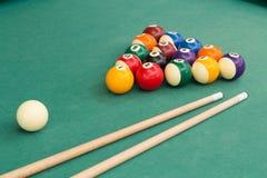 Encurralar bolas de associação dos billards e vara de sugestão na tabela verde imagem de stock