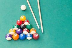 Encurralar bolas de associação dos billards e vara de sugestão na tabela verde foto de stock