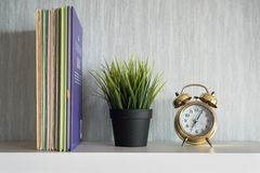 Encyclopedia books, plant and alarm clock on white shelf. Get organized concept and home interior design concept royalty free stock photos