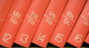 Encyclopedia in a Bookshelf (Close View). Close view on red books standing in a bookshelf Royalty Free Stock Photo