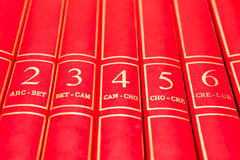 Encyclopedia. Row of red encyclopedia books on a shelf royalty free stock images