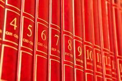 Encyclopedia. Row of red encyclopedia books on a shelf stock photo