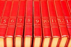 Encyclopedia. Row of red encyclopedia books on a shelf stock image