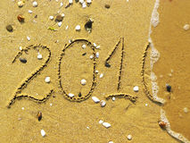 End of 2010 on the beach. 2010 written on the beach and one wavelet erasing it Stock Photo