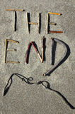 The End. Words The End spelled out in driftwood on a beach stock image