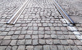End of abandoned tramway railroad in the city. Stone pavement and rails perspective Royalty Free Stock Images