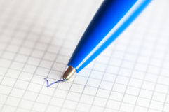 The end of a ballpoint pen on notebook background. Close-up Royalty Free Stock Image