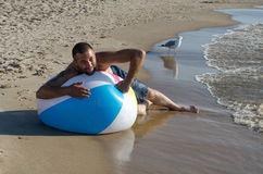 End of beach day. A man tries to deflate a large beach beach ball so he can pack up everything and go home. end of a nice beach day Royalty Free Stock Image