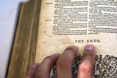 The end. A hand pointing to the last words in a book, the end. Written in old english, with end written as ende Royalty Free Stock Photography