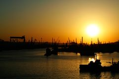 End of a busy day. Low evening sun glows over a busy industrial harbor Royalty Free Stock Images