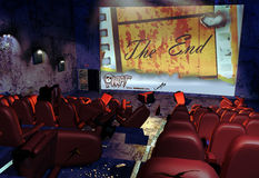End of cinema. Interior of a devastated cinema, with broken chairs, garbage and cinema tickets on the floor, and graffiti on the door and screen. One of the Royalty Free Stock Photo