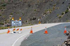 End of closed road in the mountains. Road closed sign on street with orange  traffic cones and blinking lights Royalty Free Stock Images