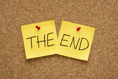 The End concept. The End written on two yellow sticky notes on an office cork bulletin board Stock Image