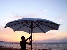 End of The Day. Waitertaking down umbrellas atsunset Stock Photos