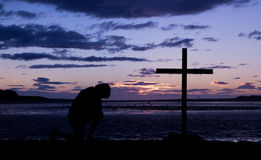 End Of Day Cross. As the day ends a man kneels in pray before a cross Royalty Free Stock Photography