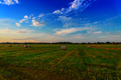 End of day over field with hay bale Royalty Free Stock Images