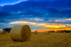 End of day over field with hay bale Stock Image