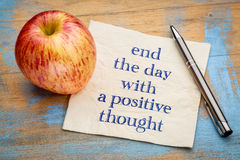End the day with a positive thought. Handwriting on a napkin with a fresh apple Royalty Free Stock Images
