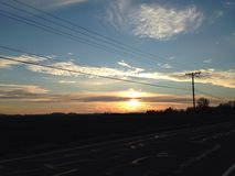 End of the day on the road. Sunsetting phone pole back roads grass field Royalty Free Stock Photos