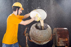 Worker is cleaning cement mixer while big rain is falling Royalty Free Stock Photos