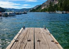 At the end of a dock in the high Sierras at Echo Lake near Tahoe in California. A weathered wooden dock meets the fresh waters of the high elevation Echo Lake in stock image