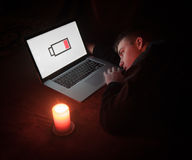 End of electricity. Laptop showing Low Battery sign with a desperate man. A candle showing that there is no more electricity Stock Photography