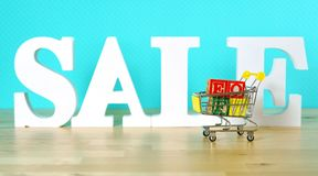 End of Financial Year sales shopping concept. With mini shopping cart and large sale letters royalty free stock image