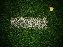 End of football season. Dry birch leaf fallen on ground of plastic green football turf with painted white line . Dramatic colors. Stock Photo