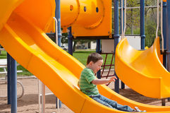 End of the Fun Slide. Little boy enjoying the playground equipment at the city park Stock Images