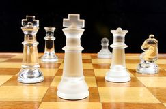 End Game. Glass Chess Pieces on a wooden chessboard Stock Photo