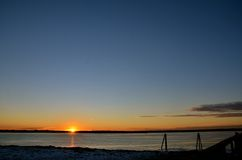The end of a great winter day in New England. Good bye to the sun shine over the ocean on a cold winter day in New England Royalty Free Stock Image